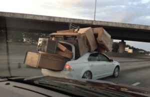 a competitor hauling old furniture stacked up really high